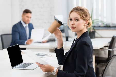 Businesswoman with paper cup looking at camera, while holding paper sheet at workplace on blurred background