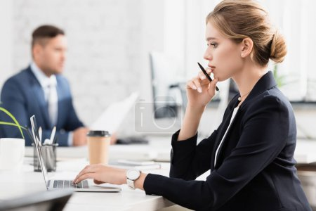 Photo for Side view of thoughtful businesswoman with pen typing on laptop, while sitting at workplace on blurred background - Royalty Free Image