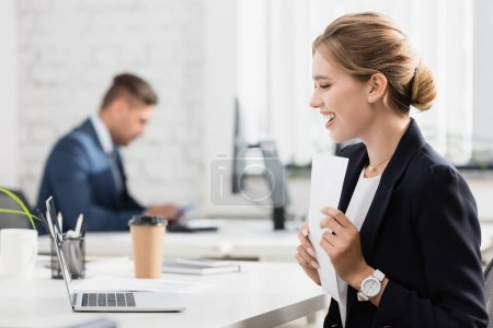 Happy businesswoman with paper sheet looking at laptop, while sitting at workplace on blurred background
