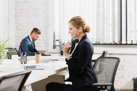 Cheerful businesswoman looking at laptop, while sitting at workplace on blurred background