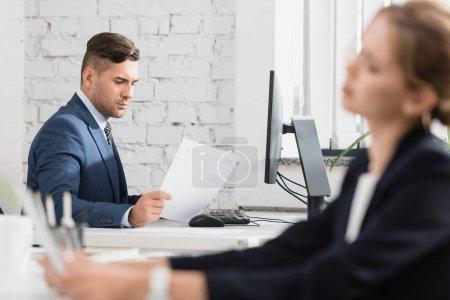 Photo pour Homme d'affaires concentré regardant une feuille de papier, assis à table sur le premier plan flou - image libre de droit