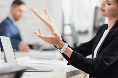 Photo for Cropped view of sad businesswoman gesturing, while sitting near laptop at workplace on blurred background - Royalty Free Image