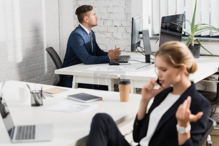 Focused businessman sitting at workplace with blurred colleague talking on phone on foreground