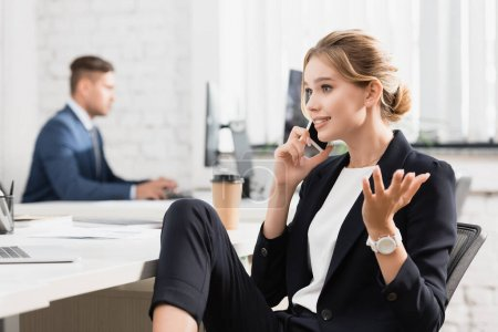 Positive businesswoman gesturing, while talking on mobile phone at workplace on blurred background
