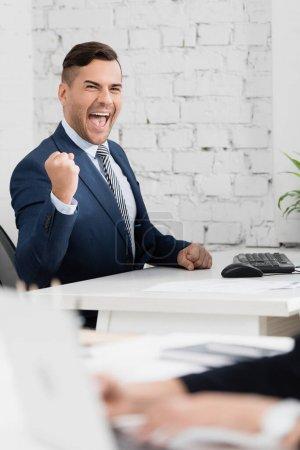 Emocionado hombre de negocios con sí gesto mirando a la cámara, mientras se sienta en la mesa en la oficina en primer plano borrosa