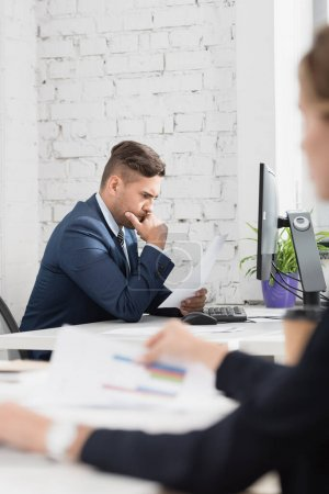 Photo for Thoughtful businessman looking at paper sheet, while sitting at workplace on blurred foreground - Royalty Free Image
