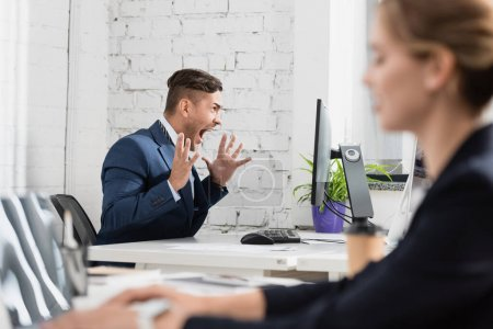 Shocked businessman with open mouth looking computer monitor, while sitting at workplace on blurred foreground