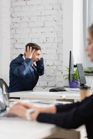 Geschockter Geschäftsmann mit händchennahem Kopf, der auf den Computermonitor blickt, während er am Arbeitsplatz im verschwommenen Vordergrund sitzt