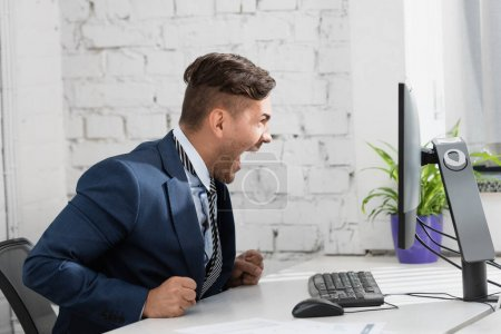 Shocked businessman with open mouth looking at computer monitor, while sitting at workplace