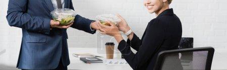 Photo pour Vue recadrée d'une femme d'affaires souriante prenant un bol en plastique avec de la nourriture de son collègue, assis sur le lieu de travail, bannière - image libre de droit