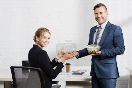 Photo pour Des gens d'affaires souriants avec repas dans des bols en plastique, regardant la caméra pendant la pause au bureau - image libre de droit
