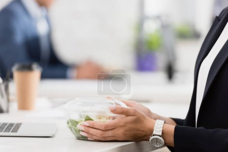 Cropped view of female executive holding plastic bowl with meal at workplace on blurred background