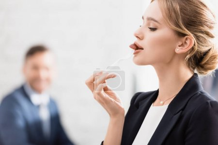Blonde businesswoman eating with plastic fork during break in office on blurred background