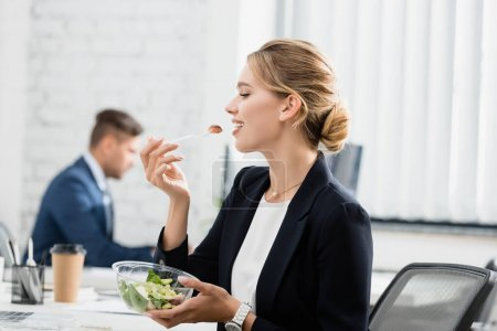 Blonde businesswoman eating meal from plastic bowl, while sitting at workplace on blurred background