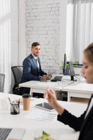 Geschäftsmann mit Mahlzeit in Plastikschüssel und Gabel schaut Kollegen an, während er am Arbeitsplatz im verschwommenen Vordergrund sitzt