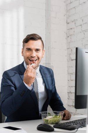 Lächelnder Geschäftsmann blickt in die Kamera, während er am Arbeitsplatz Essen aus Plastikschüssel isst
