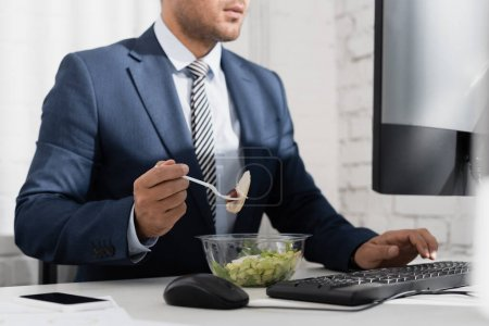 Cropped view of businessman eating meal from plastic bowl, while typing on computer keyboard at workplace