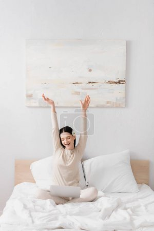 amazed freelancer with vitiligo sitting with hands above head and looking at laptop in bedroom