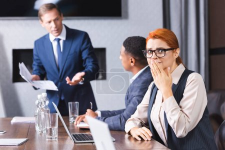 Photo for Scared businesswoman covering mouth with hand and looking at camera while sitting near blurred multicultural colleagues on background - Royalty Free Image