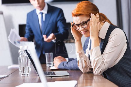 Photo for Scared redhead businesswoman with hands near head squinting while sitting near colleagues on blurred background - Royalty Free Image