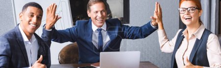Photo for Happy businessman giving high five to multicultural colleagues with thumbs up at workplace in meeting room, banner - Royalty Free Image