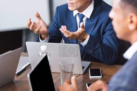Photo for Cropped view of executive gesturing while sitting at workplace near blurred african american businessman on foreground - Royalty Free Image
