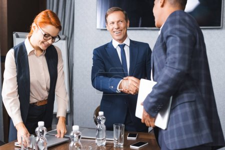 Photo for Smiling businessman shaking hands with african american colleague while standing near businesswoman in meeting room - Royalty Free Image