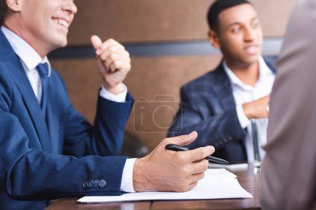Investor with pen near papers sitting near african american businessman at workplace on blurred foreground