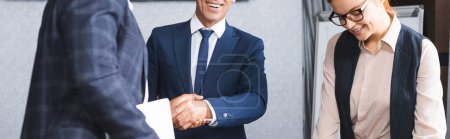 Photo for Businessmen shaking each other hands near smiling redhead businesswoman in meeting room, banner - Royalty Free Image