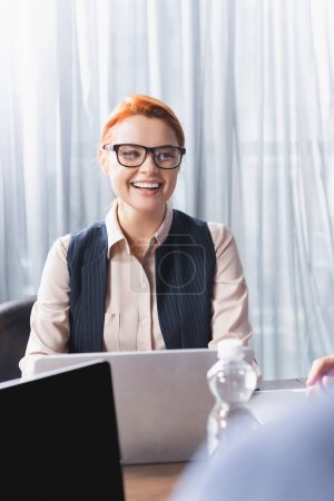 Cheerful businesswoman in eyeglasses sitting at workplace with laptops while looking at blurred colleague on foreground