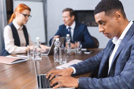 Photo pour Homme d'affaires afro-américain concentré tapant sur ordinateur portable sur le lieu de travail avec des collègues flous sur fond - image libre de droit