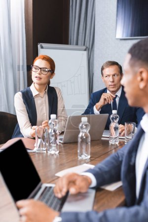 Redhead businesswoman talking while sitting at workplace with multicultural colleagues on blurred foreground in meeting room