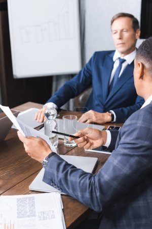 African american businessman pointing with pen at document while sitting near thoughtful executive on blurred background