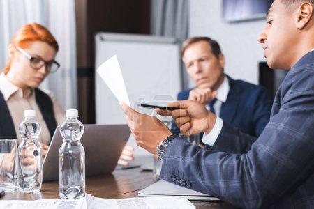 Afrikanischer Geschäftsmann zeigt mit Stift auf Papier in der Nähe von Kollegen und Führungskräften auf verschwommenem Hintergrund im Sitzungssaal