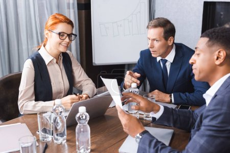 Serious executive pointing with finger at paper in hands of african american man while looking at businesswoman in boardroom