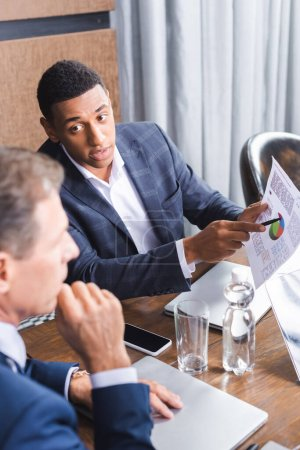African american businessman pointing with pen at graph on paper while looking at blurred executive thinking on foreground