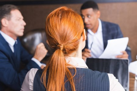 Back view of redhead businesswoman with blurred colleagues discussing on background in meeting room