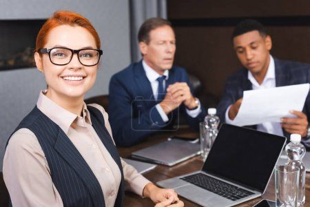 Smiling businesswoman looking at camera while sitting at workplace with digital devices and blurred colleagues on background