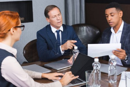 Photo for Executive pointing with finger at paper in hands of african american businessman at workplace on blurred foreground - Royalty Free Image