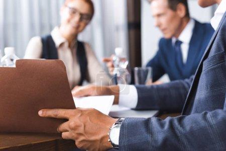 Foto de Vista de cerca de la carpeta de papel de apertura del empresario afroamericano en el lugar de trabajo con empresarios borrosos en el fondo - Imagen libre de derechos