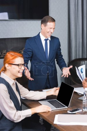 Happy executive laughing while standing near multicultural colleagues at workplace on blurred foreground in boardroom