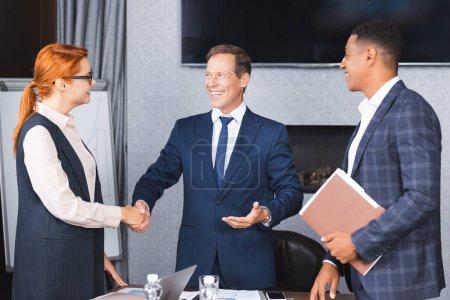 Foto de Smiling businesspeople que se estrechan la mano mientras que está parado cerca de colega afroamericano en sala de juntas - Imagen libre de derechos