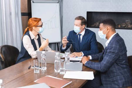 Photo for Multicultural businesspeople in medical masks talking with investor while sitting at workplace with digital devices - Royalty Free Image