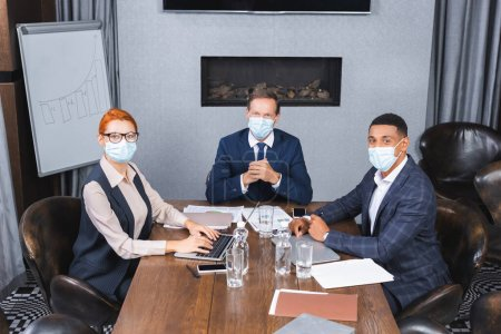 Multicultural businesspeople in medical masks looking at camera while sitting at workplace with digital devices in meeting room