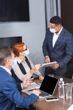 African american businessman in medical mask with paper folder looking at female executive sitting near colleague at workplace