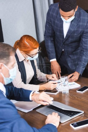 Photo for Multicultural businesspeople pointing with pens at document at workplace in boardroom with blurred colleague on foreground - Royalty Free Image
