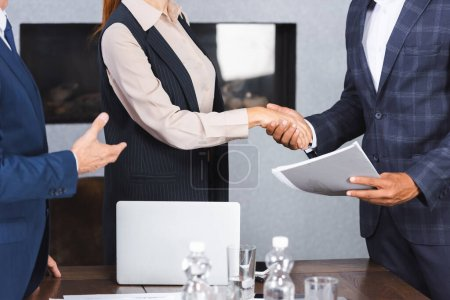 Photo for Cropped view of multicultural businesspeople shaking hands with each other near colleague in meeting room - Royalty Free Image