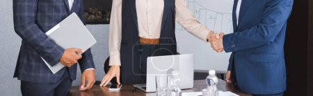 Cropped view of african american businessman standing near colleagues shaking hands with each other in boardroom, banner