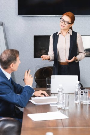 Female executive gesturing while talking to colleague sitting at workplace during business meeting
