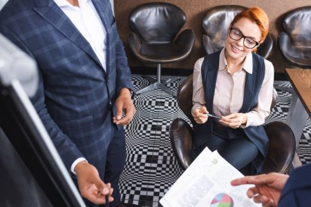High angle view of smiling redhead executive sitting near colleagues talking near blurred flipchart on foreground